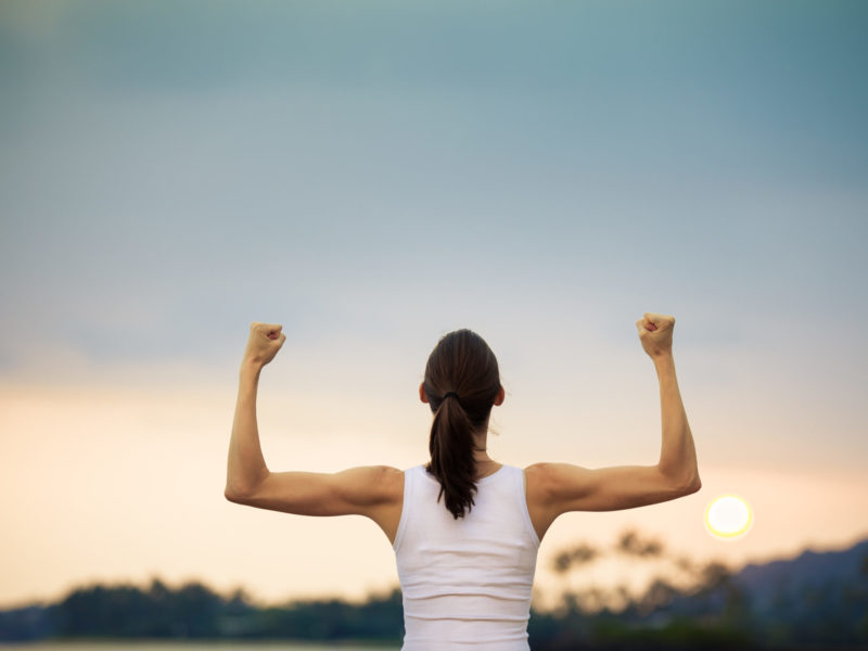 photo of a strong woman with arms uplifted celebrating sustainable weight loss in front of a sunset